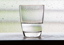 Glass with half a glass of water scenes with condensation glass. Royalty Free Stock Photos