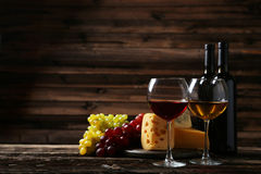 Glass of red and white wine, cheeses and grapes on the brown wooden background Royalty Free Stock Photography