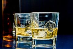 Glasses of alcoholic drink with ice on blue light Royalty Free Stock Image