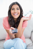 Gleeful cute brunette sitting on couch holding remote Stock Images