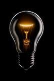 Glowing lamp on black Stock Image