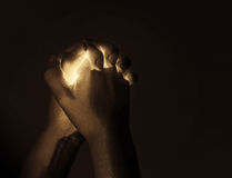 Glowing in praying hands Stock Images