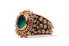 Golden ring with precious green gem Stock Photos