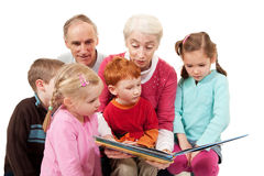 Grandparents reading kids story book to children Stock Image