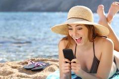 Grappige verraste vrouw die op sociale media in een slimme telefoon op het strand letten Stock Afbeelding