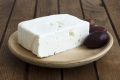 Greek feta cheese with kalamata olives on rustic plate and table Stock Photography