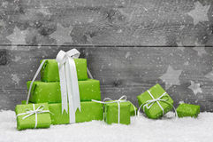 Green Christmas presents with snow on grey wooden background for Royalty Free Stock Images