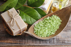 Green sea salt and bar of natural handmade soap on wooden table Stock Image