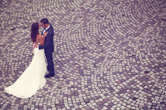 Groom and bride on bricks pavement Royalty Free Stock Image