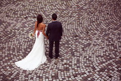 Groom and bride on pavement Stock Photos