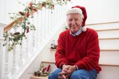 Grootvader die Santa Hat Sitting On Stairs dragen bij Kerstmis Stock Afbeeldingen
