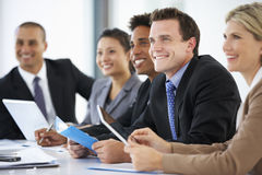 Group Of Business People Listening To Colleague Addressing Office Meeting Royalty Free Stock Images
