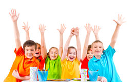 Group of children in colored t-shirts with raised hands. Royalty Free Stock Image