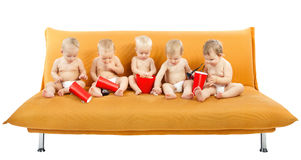 Group of children sitting on sofa, eating popcorn Stock Photography