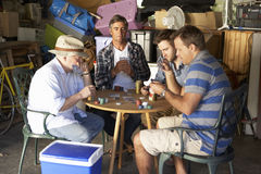 Group Of Male Friends Playing Cards In Garage Royalty Free Stock Photos