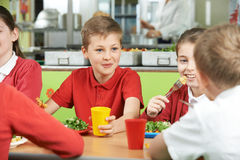 Group Of Pupils Sitting At Table In School Cafeteria Eating Meal Stock Photography