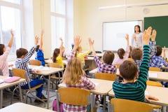 Group of school kids raising hands in classroom Stock Image