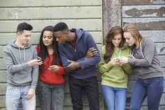Group Of Teenagers Sharing Text Message On Mobile Phones Stock Images