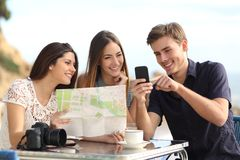 Group of young tourist friends consulting gps map in a smart phone Royalty Free Stock Photography