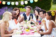 Grupo de amigos que disfrutan del partido de cena al aire libre Imagenes de archivo