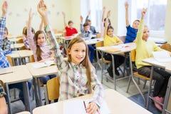 Gruppe der Schule scherzt das Anheben von Händen im Klassenzimmer Lizenzfreie Stockfotos