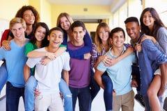 Gruppe hohe Schüler, die Doppelpol im Korridor geben Stockbilder