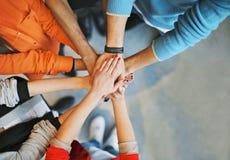 Gruppe junge Leute, die ihre Hände stapeln Lizenzfreies Stockfoto