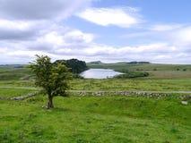 Guardando al Lough delle rupe sopra la parete di Hadrian Immagini Stock