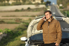 Guy calling roadside assistance for his breakdown car Stock Images