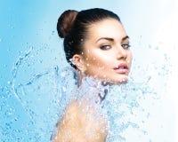 Härlig flicka under färgstänk av vatten Arkivbilder