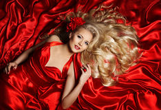 Hair Model, Fashion Woman Blonde Lying on Red Silk Cloth Stock Photography