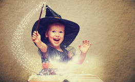 Halloween. cheerful little witch with a magic wand and glowing b Stock Image