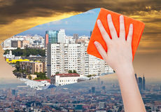 Hand deletes smog in city by orange cloth Royalty Free Stock Photography
