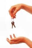 Hand giving away house keys Stock Photos