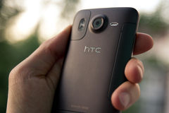 Hand hold HTC Desire HD smartphone Stock Photography