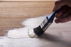 Hand holding a brush applying  varnish paint Royalty Free Stock Photography