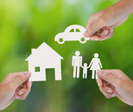 Hand holding paper home, car, family on green background Stock Photos