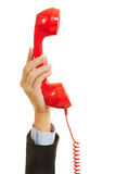 Hand holding red phone for emergency call Royalty Free Stock Photos