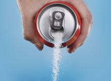 Hand holding soda can pouring a crazy amount of sugar in metaphor of sugar content of a refresh drink Royalty Free Stock Photo