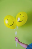 Hand holding two happy balloons Stock Photography