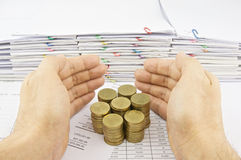 Hand of man protect stack of gold coins Royalty Free Stock Images