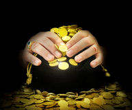 Hands on a bag of gold coins Stock Photo