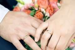 Hands of happy newly-married couple with gold wedding rings and flowers Stock Photo