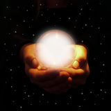 Hands holding glowing crystal ball Stock Photo