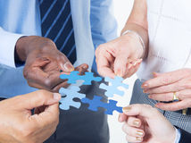 Hands Holding a Jigsaw with Business Concepts Royalty Free Stock Photography