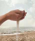 Hands holding and spilling sand with beach in the background Royalty Free Stock Photos