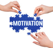 Hands with puzzle making MOTIVATION word Stock Images