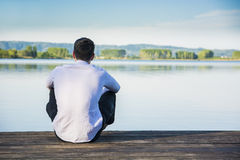 Handsome young man on a lake in a sunny, peaceful Stock Photo