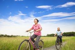 Happy Asian elderly seniors couple biking in farm Stock Photo