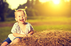 Happy baby girl laughing on hay in summer Stock Photos